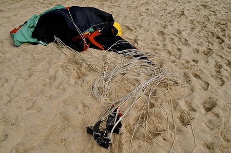 A parasail and harness are left on a sandy beach awaiting the next rider.