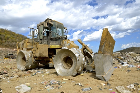 earthmover: A huge tractor with a front end loader and metal wheels is used to move trash in a city dump Stock Photo