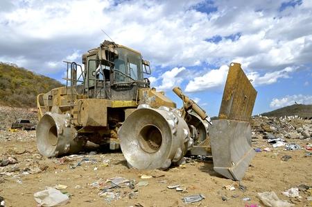 cargador frontal: Un gran tractor con un cargador frontal y ruedas de metal se usa para mover basura en un basurero de la ciudad