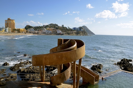 The Carpa Olivera,  a public saltwater swimming and waterslide area with the skyline of Mazatlan in the background