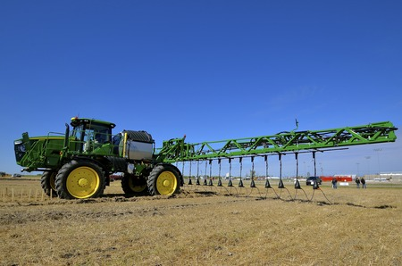 pesticides: WEST FARGO, NORTH DAKOTA, September 13, 2016. A new John Deere computerized spraying tractor and booms is doing a field demonstration on usage at the annual Big Iron Farm Show located at the Red River Fairgrounds.