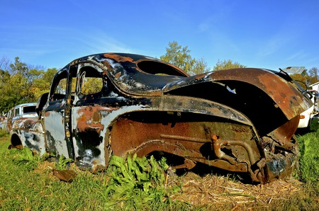 An old car full of patina rusting in a country junkyard Stock Photo