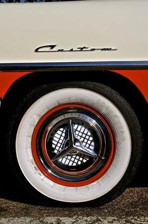sidewall: BISMARCK, NORTH DAKOTA, August 6, 2016: The Capital AFair in Bismarck features the Fords and Mustangs car show whereof a 1956 Ford Fairlane Custom 500 tire and hubcap are displayed.