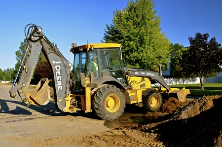 MOORHEAD, MINNESOTA, August 29,2016: The John Deere backhoe and front end loader  which is scooping sand in a road project is a product of John Deere Co, an American corporation that manufactures agricultural, construction, forestry machinery, diesel engi