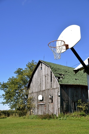 Basketball hoops on the side of  an old weathered hip roofed barn