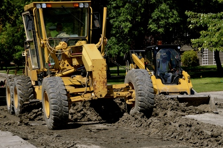 grader: A road grader blades moves earth in a road repair construction street project of a residential neighborhood.