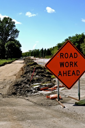 A Road Work Ahead sign warns of sidewalk, curb, and street repair Stock Photo