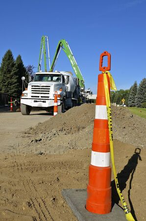A pumper ready mix truck with a pumper brings wet concrete for a street, sidewalk, and curb repair project Stock Photo