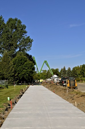 A freshly poured concrete sidewalk with a cement ready mix pumper truck in the distance at a construction site Stock Photo