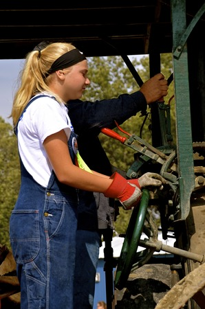 annually: ROLLAG, MINNESOTA, Sept 2, 2016: An unidentified girl operates an old restored steam engine in a parade at the West Central Steam Threshers Reunion in Rollag, MN attended by 1000s held annually on Labor Day weekend.