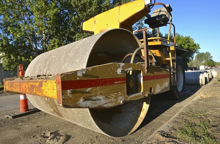 prior: A heavy  industrial roller packs the top layer of sand prior to the applying of a new layer of asphalt on a street construction project