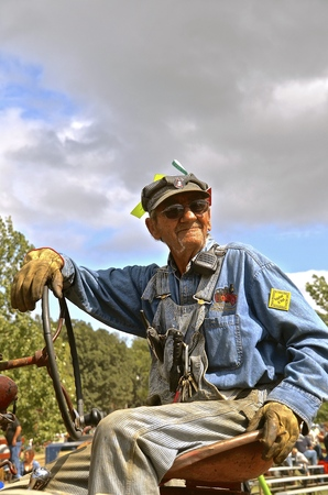ROLLAG, MINNESOTA, Sept 2, 2016: An official unidentified man wearing tags, a ring  keys, and driving an old tractor at the West Central Steam Threshers Reunion in Rollag, MN attended by 1000s held annually on Labor Day weekend. Editorial