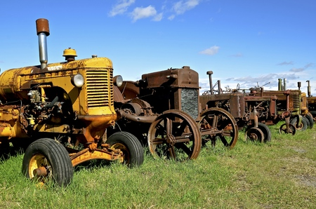 A row of old rusty worn tractors stand  in a row bringing back old farming memories. Stock Photo