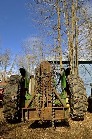 Kettingen voor meer tractie in modder, ijs en sneeuw zijn op de achterband van een tractor geplaatst