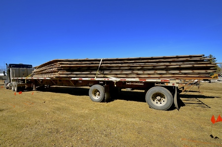 A truck load of salvaged rafters are loaded unto a flat bed semi truck and trailer Stock Photo