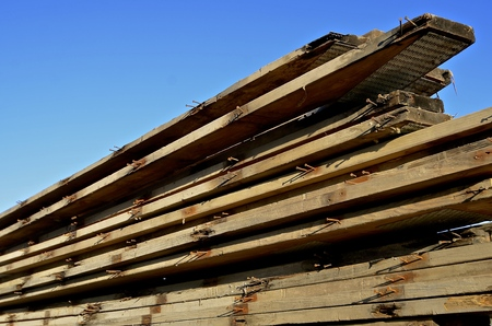 rafters: Rust coated nails stick out of reclaimed dimension wood boards used for rafters