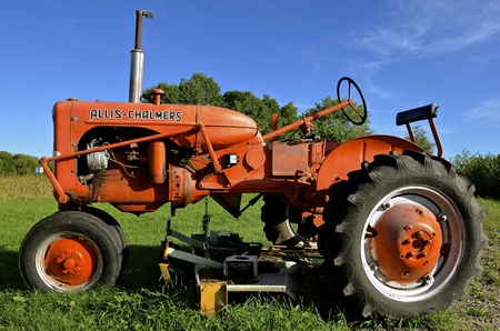 ALEXANDRIA, MINNESOTA, August 12, 2016: The restored orange tractor with a belly mower is an Allis Chalmers , a U.S. manufacturer of machinery for various industries including agricultural equipment, construction, power generation, and power transmission. Editorial