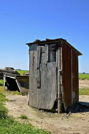 latrine: An old rickety outhouse construction from various pieces of weathered wood