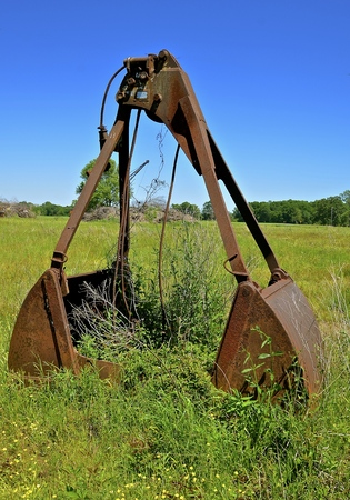 An old scoop from a crane to move earth, objects, or rock is left abandoned in the long grass.