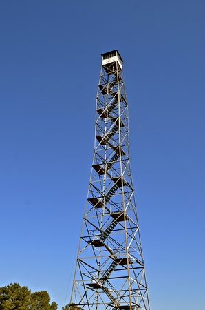 An old historic metal fire tower reaches high into the blue sky with a forest below. Stock Photo