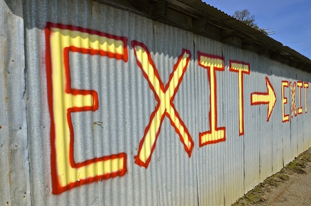 Brightly colored exit sign printed on a steel corrugated building  provides directions with an arrow. Stock Photo