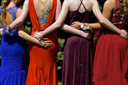 Meisjes in kleurrijke prom dresses met armen om elkaar heen als ze polscorsages dragen