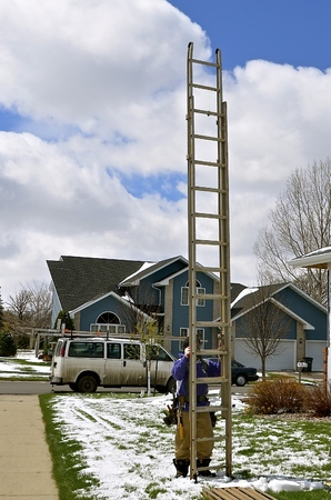 An unidentified construction worker is moving a ladder on a house construction project Stock Photo