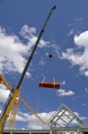 hydraulic lift: A huge crane lifts a section of a pipe to a building under construction.