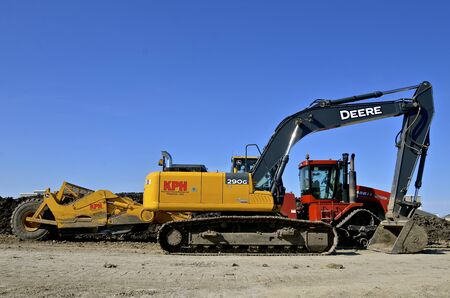 cargador frontal: FARGO, DAKOTA DEL NORTE, 5 de mayo de 2017: La enorme excavadora cargadora de pala de la parte delantera es un producto de John Deere Co, una corporación americana que fabrica maquinaria agrícola, construcción, silvicultura, motores diesel y drivetrains.