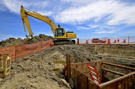 Excavating machine at a road construction site with safety fences surrounding project Stock Photo