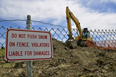 Sign warning of no snow pushed against the construction barrier fence during the summer. Stock Photo