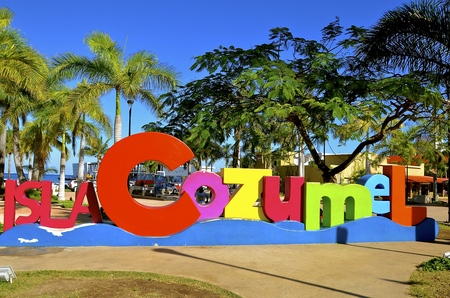 A colorful sign welcome tourists and visitors arriving to Cozumel as they enjoy the palm trees and tropical environment