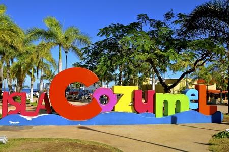 Un segno colorato accoglie turisti e visitatori che arrivano a Cozumel mentre si godono le palme e l'ambiente tropicale Archivio Fotografico - 78563671