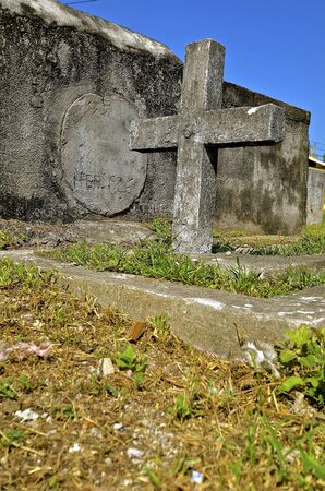 A  very old cross and tomb in an unkempt cemetery is in memory of an unknown person