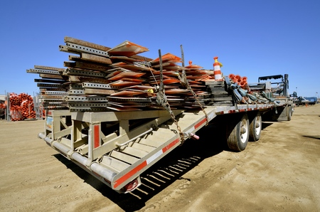 signo pesos: A trailer and truck is loaded with construction signs and equipment for a road project