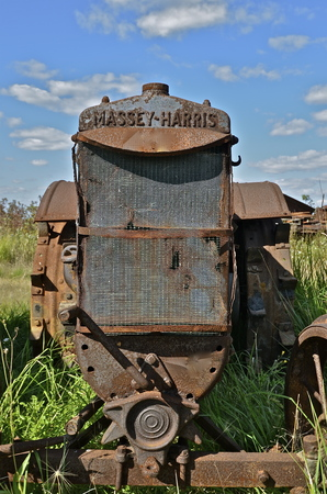 traction engine: BARNESVILLE, MINNESOTA, September 14, 2014: The Massey Harris name on the rusty tractor with missing parts disappeared when a merger of Massey Harris and the Ferguson Company farm machinery manufacturer occurred in 1953, to become Massey Ferguson.