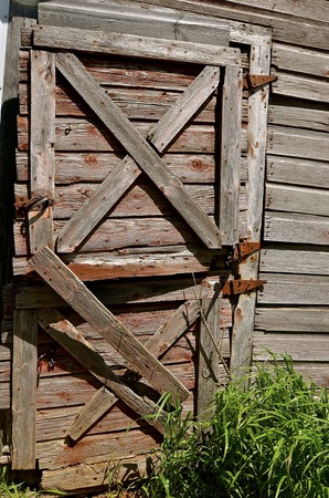 Faded Red Peeling And Rickety Old Barn Or Stable Door Stock Photo