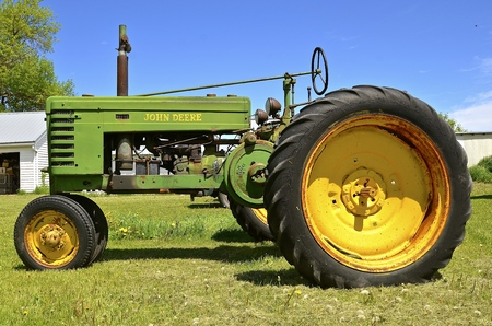 Osakis, MINNESOTA, May 25, 201: A John Deere tractor parked in the grass is a product of John Deere Co, an American corporation that manufactures agricultural, construction, forestry machinery, diesel engines, and drivetrains.