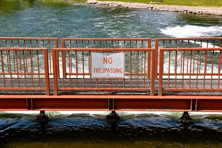 A No Trespassing sign is displayed in front of a dam spillway by a historic old grist mill.