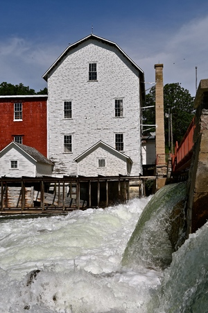 Water pours over a dam by an old historic grist mill