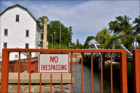 A No Trespassing sign is located by an old dam and flour grist mill Stock Photo