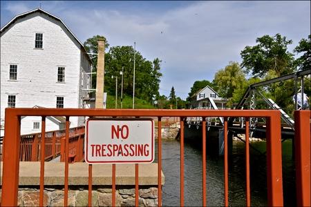 """prohibido el paso: Un letrero """"No Trespassing"""" está ubicado cerca de una antigua presa y molino de harina Foto de archivo"""