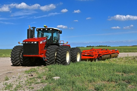 HALSTAD, MINNESOTA, June 5, 2015: The 450 Versatile 4 wheel drive tractor pulling a field cultivator was produced by Versatile  a Canadian brand of agricultural equipment that has also produced augers, swathers, and combine harvesters and now owned by Ros