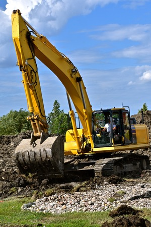 Unidentified excavating operator moves earth in a summer construction project Stock Photo