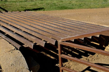 A  closeup of a metal grated cattle guard crossing a gravel road