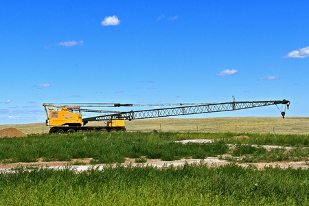 dragline: An old crane with a long boom is left in the grass of the western rolling prairies Stock Photo