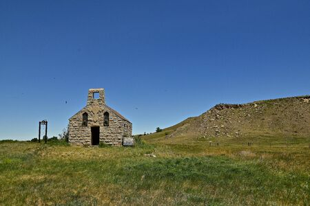 An old abandoned church is situated in front of a rocky butte