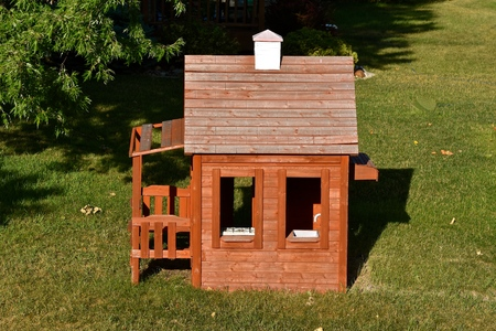 A childs backyard play house with a porch,  stove, sink and chimney. Stock fotó