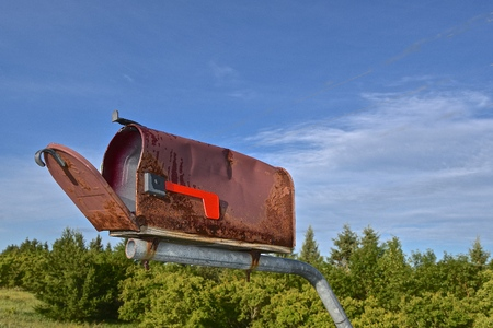 Open lid to an old rusty mailbox located in the rural country Stock Photo