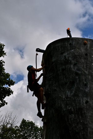 An unidentified wall climber is silhouetted at the top of the climb.